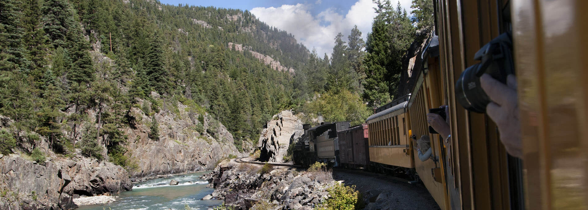 Train Next to River and Mountains